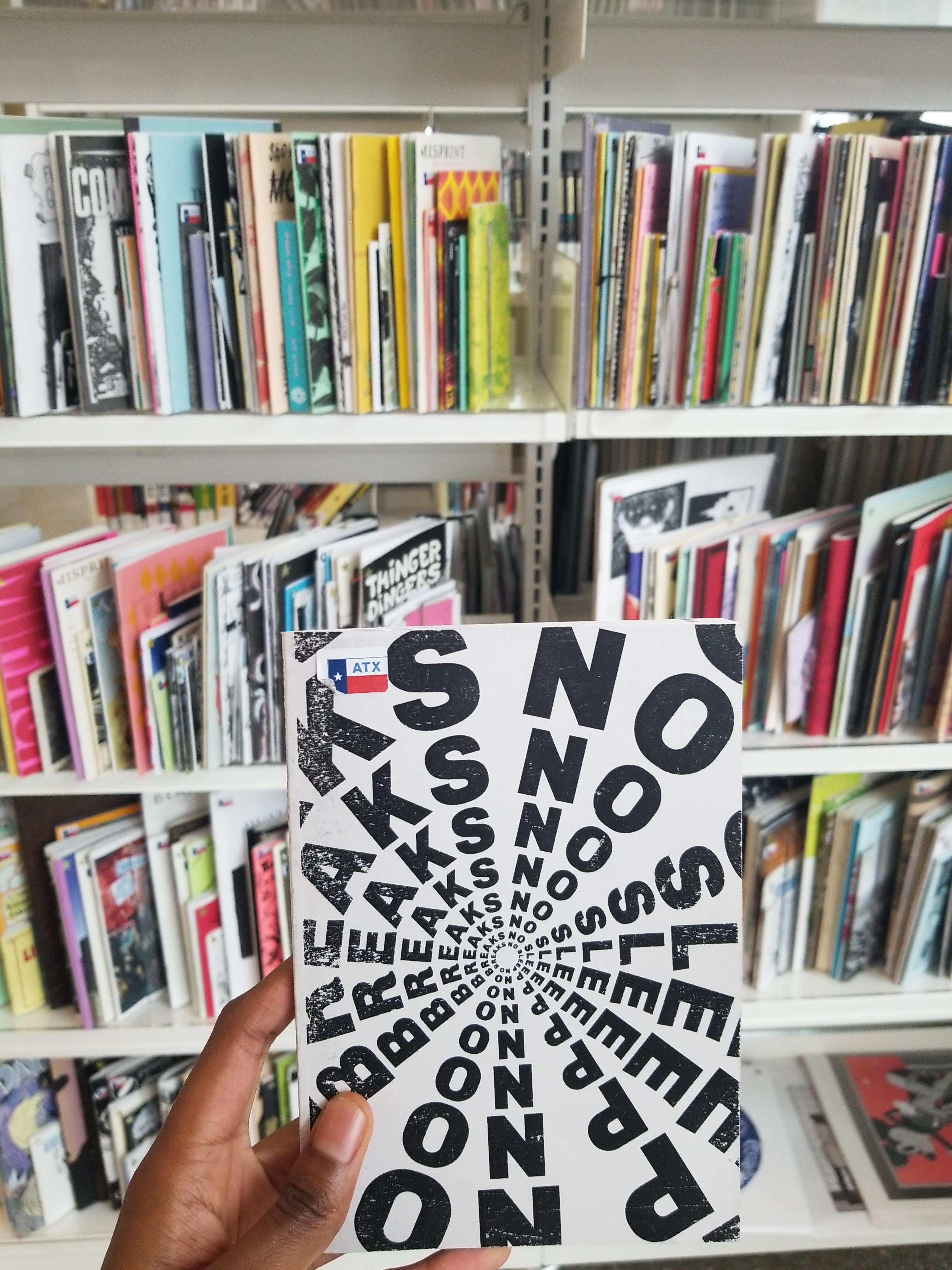 My hand holding a copy of NSNB at the Austin Public Library.