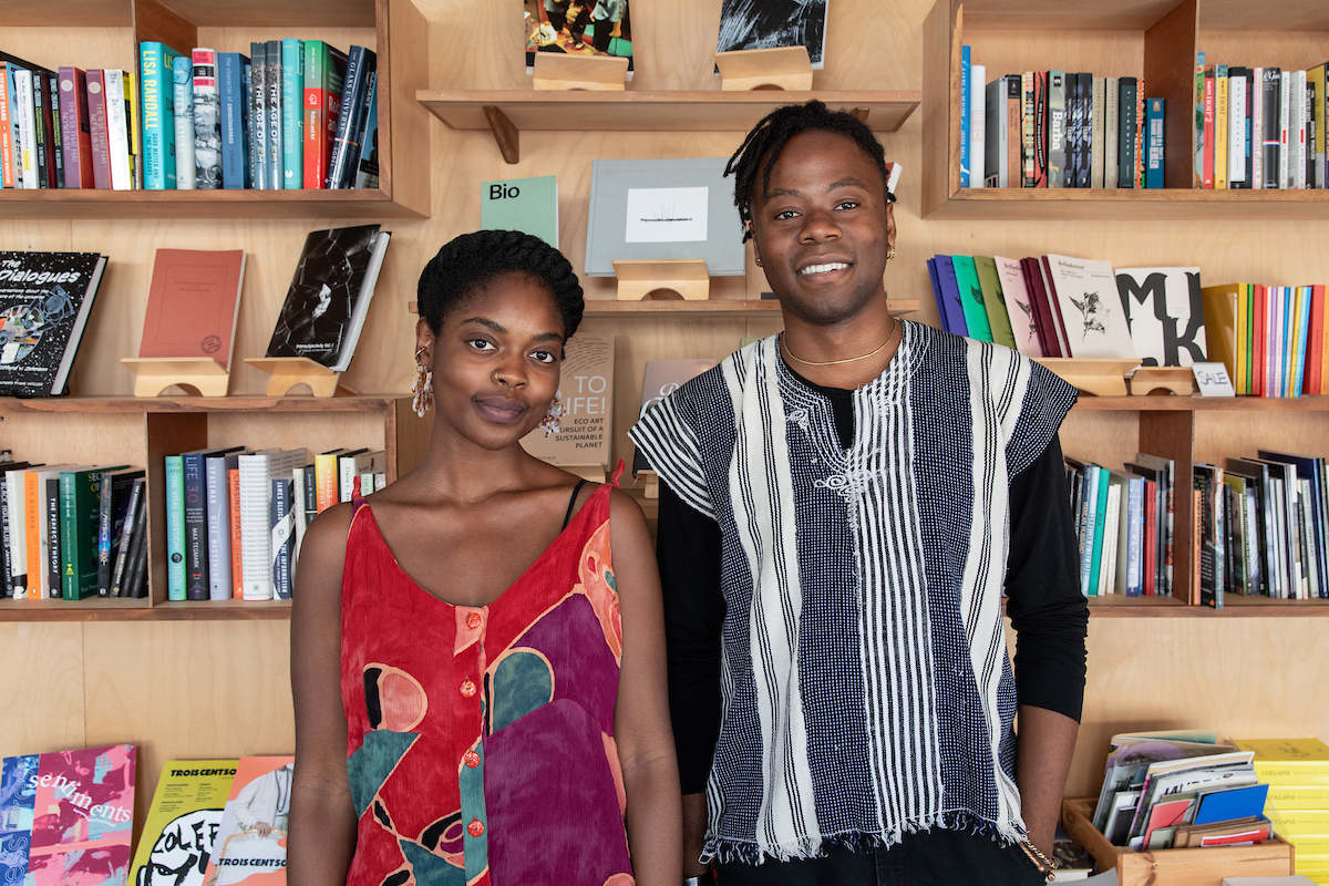 Bomani McClendon (right) and Neta Bomani (left) in front of a bookshelf at Pioneer Books.